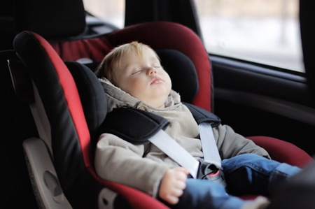 enfant qui dort: Portrait de garçon bambin dormir dans le siège de voiture Banque d'images