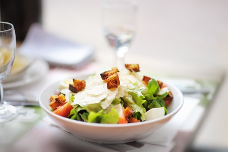 chicken salad: Fresh salad with parmesan cheese and croutons, chicken and tomato on table