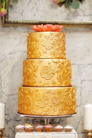 wedding table decor: Sweet table with big golden cake for wedding party