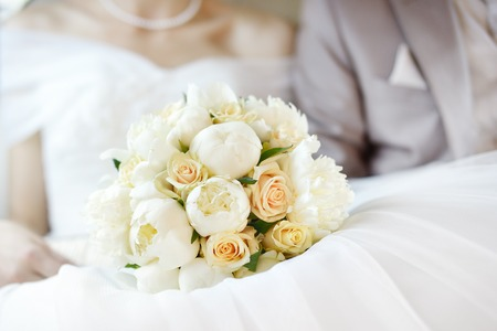 anniversary flowers: Wedding flowers bouquet with newlywed couple on background Stock Photo
