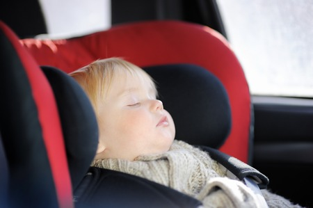 Portrait of sweet toddler boy sleeping in car seat photo