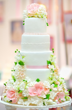 cake stand: White wedding cake decorated with cream flowers