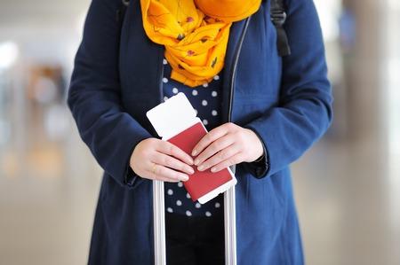 foto carnet: Cierre de la foto de la mujer que sostiene el pasaporte y tarjeta de embarque en el aeropuerto Foto de archivo