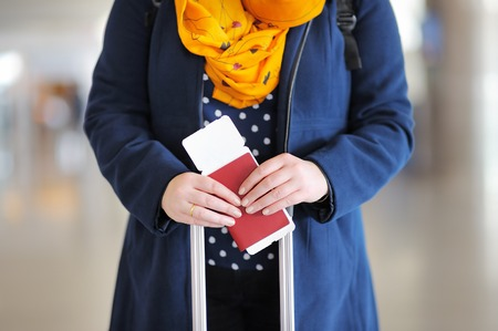 Close up photo of woman holding passport and boarding pass at the airport Standard-Bild