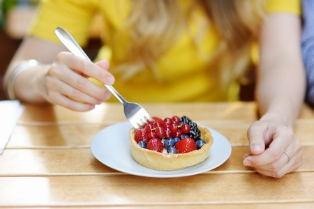 dessert plate: Young woman eating custard fruit tart in the outdoors cafe
