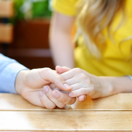 affiance: Detailed view of a young couple holding hands