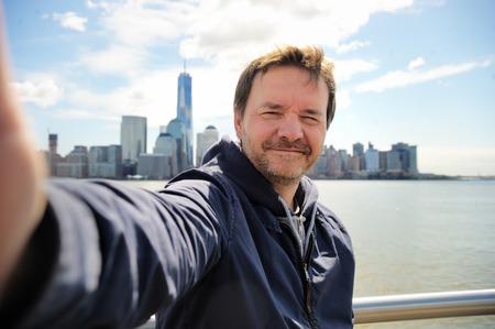 Middelbare leeftijd man het nemen van een zelfportret (selfie) met wolkenkrabbers van Manhattan in New York City