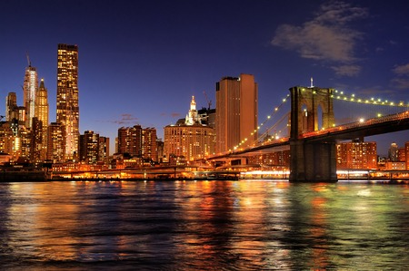 New York City Brooklyn Bridge with downtown skyline over East River at night