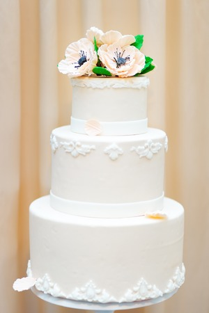 Delicious white wedding or birthday cake decorated with flowers