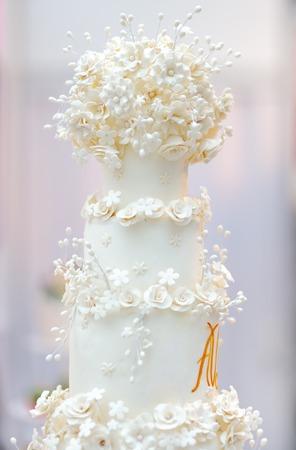 크림 꽃으로 장식 된 맛있는 흰색 웨딩 케이크