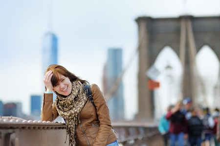 american city: Beautiful young girl on Brooklyn Bridge with skyscrapers on background
