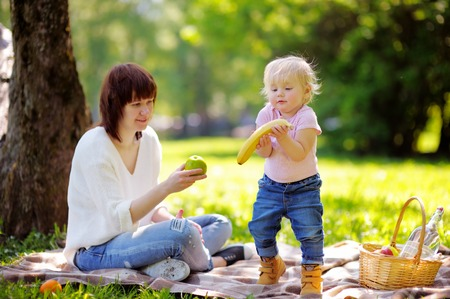 picnic cloth: Beautiful young  woman and her adorable little son having a picnic in sunny park
