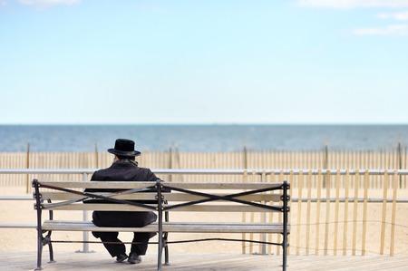 poblíž: Unrecognizable židovský muž sedí na dřevěné lavici v blízkosti oceánu