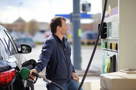 middle age man: Middle age man filling gasoline fuel in car holding nozzle Stock Photo
