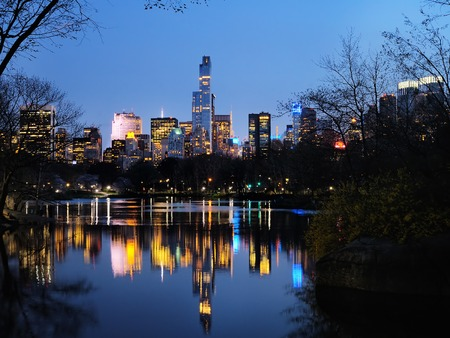 Central Park in dusk and buildings reflection in midtown Manhattan New York City