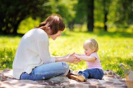 Beautiful young woman and her adorable little son having fun outdoors