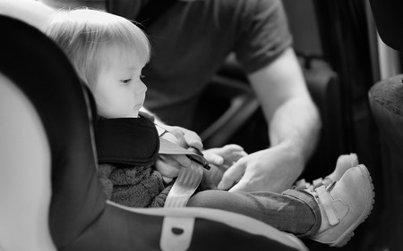 Black and white shot of toddler boy in the car seat