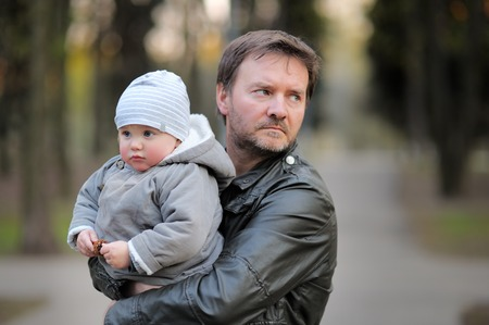Middle age father with his toddler son walking outdoors / kidnapping concept