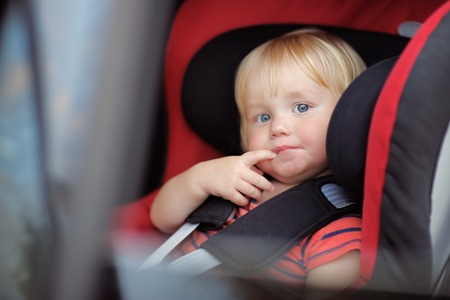 car seat: Portrait of toddler boy sitting in car seat Stock Photo