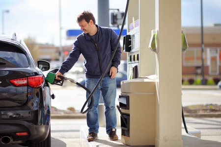fuelling station: Hombre combustible de gasolina de llenado en el coche de la celebración de la boquilla