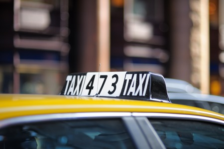 yellow taxi: Taxi sign in big city close up
