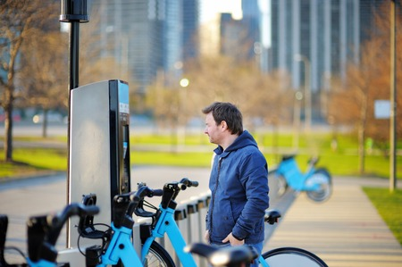 chicago city: Middle age man taking a bicycle for rent in Chicago, USA