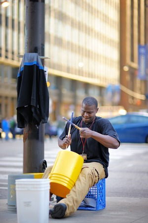 CHICAGO, USA - APRIL 24, 2015: Street musician playing rhythmical music using plastic pails on Michigan Avenue in Chicago on April 24, 2015
