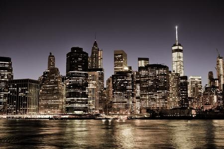 comercio: Horizonte de la ciudad de Nueva York Manhattan en la noche con los rascacielos iluminados, filtro de la vendimia