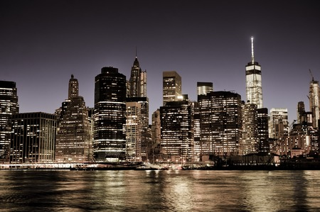 cities: New York City Manhattan downtown skyline at night with illuminated skyscrapers, vintage filter Stock Photo