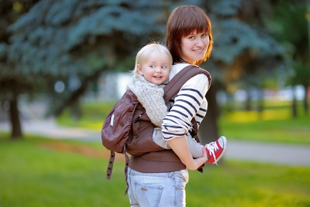 Happy young mother with her toddler child in a baby carrier