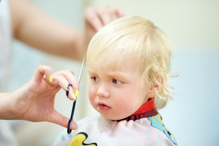 Close up portrait of toddler child getting his first haircut Stock Photo