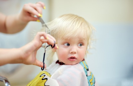 Close up portrait of toddler child getting his first haircut Standard-Bild
