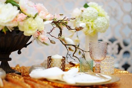 stylish: Stylish gold table set with natural flowers Stock Photo