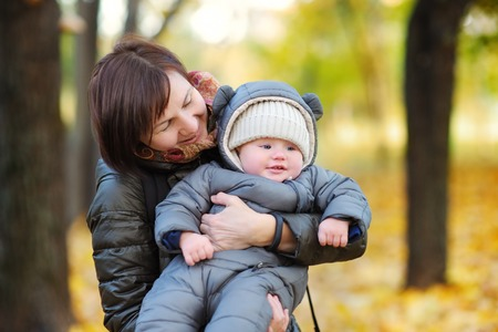 grand kids: Beautiful middle aged woman and her adorable little grandson in the autumn park Stock Photo