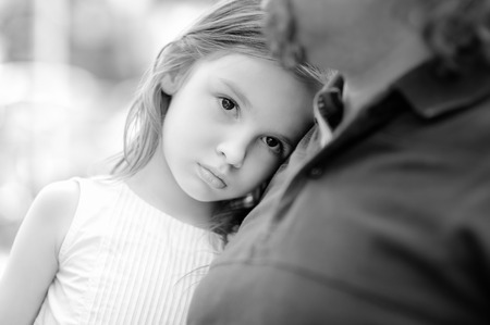 Black and white photo of sad little girl with her father