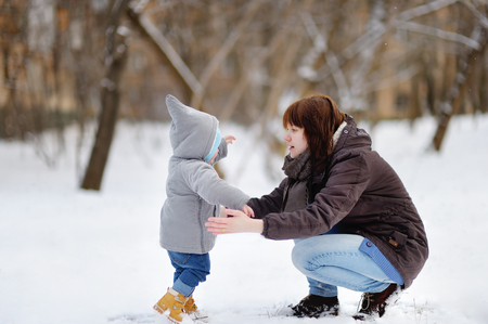 little: Little baby boy learning to walk. Young woman with her toddler boy at the winter park Stock Photo