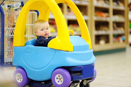 toddler boy: European toddler boy sitting in the shopping cart Stock Photo