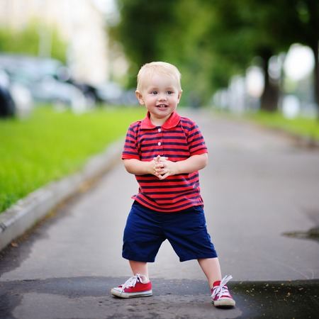 toddler boy: Toddler boy playing in the city at the spring or summer day Stock Photo