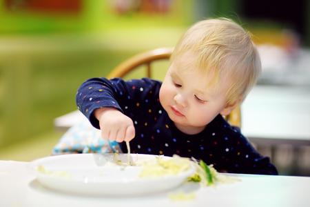 children breakfast: Toddler boy playing with food at the indoors cafe