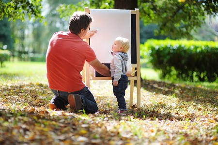 early childhood: Middle age father and his toddler son drawing outdoors Stock Photo