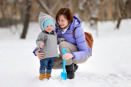 babysit: Beautiful middle aged woman and her adorable little grandson at the winter park Stock Photo