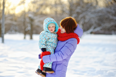 Young woman with her toddler boy at the winter park