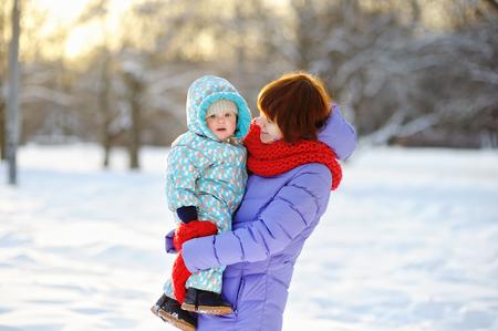 madre e hijo: Mujer joven con su niño pequeño en el parque de invierno