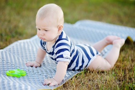 six month old: Outdoors portrait of six month old baby play with bright toy