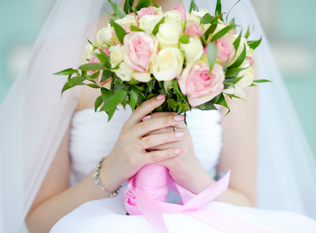 gown: Bride holding wedding flowers roses bouquet, focus in hand and wedding ring