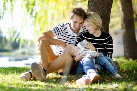 mother milk: Happy parenthood: young parents with their sweet baby girl in sunny park Stock Photo