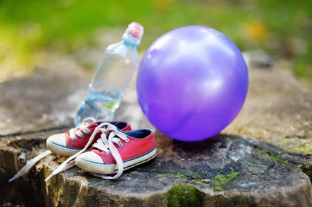 still water: Childs trainers, ball and bottle of water on wooden stump Stock Photo