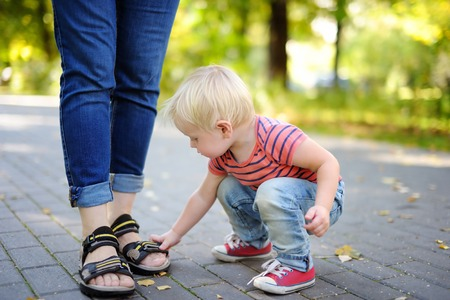 Beautiful toddler boy playing with footwear at sunny park