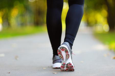 female feet: Runner feet running on road closeup on shoe. woman fitness sunrise jog workout, welness concept