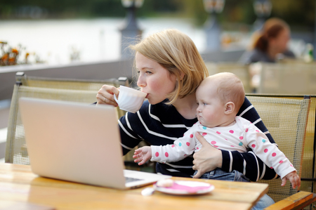 madre soltera: Joven madre con el trabajo de su bebé adorable o estudiar en su computadora portátil en el café al aire libre Foto de archivo